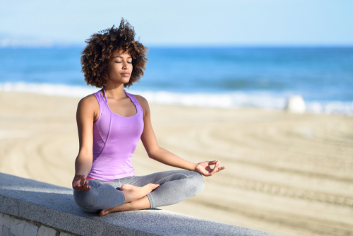 Woman practices mindfulness at the beach