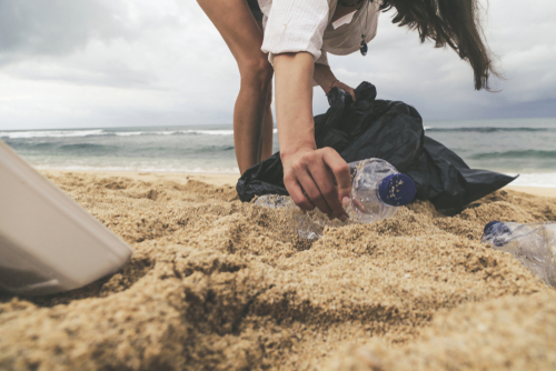 Woman picks up plastic litter off beach